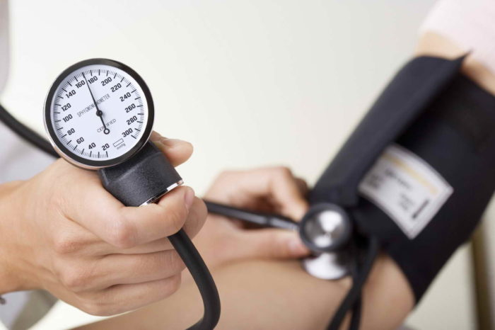 Doctor / nurse checking blood pressure with sphygmomanometer gauge in focus.