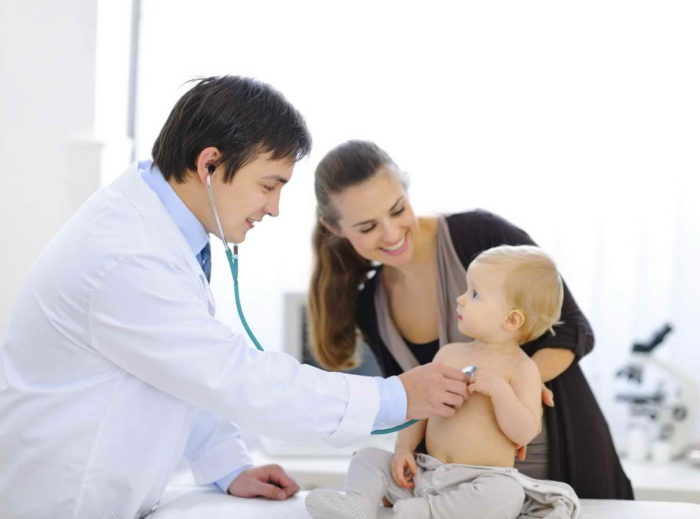 Surprised baby being checked by doctor using stethoscope