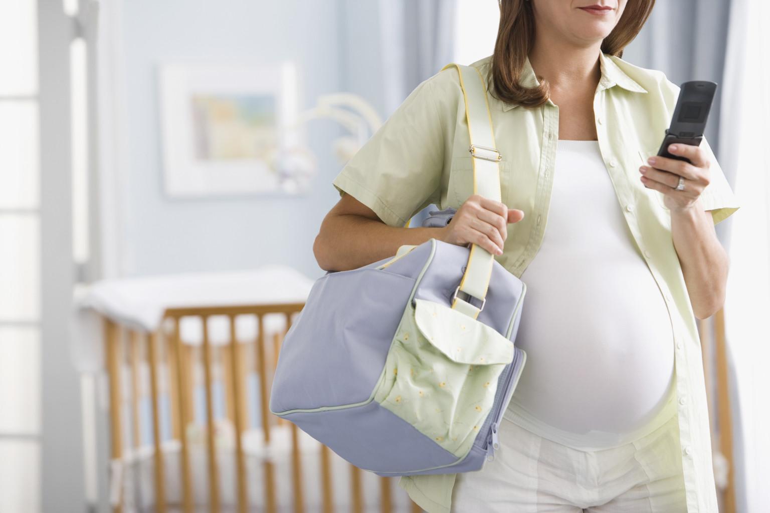 Pregnant Hispanic woman dialing cell phone