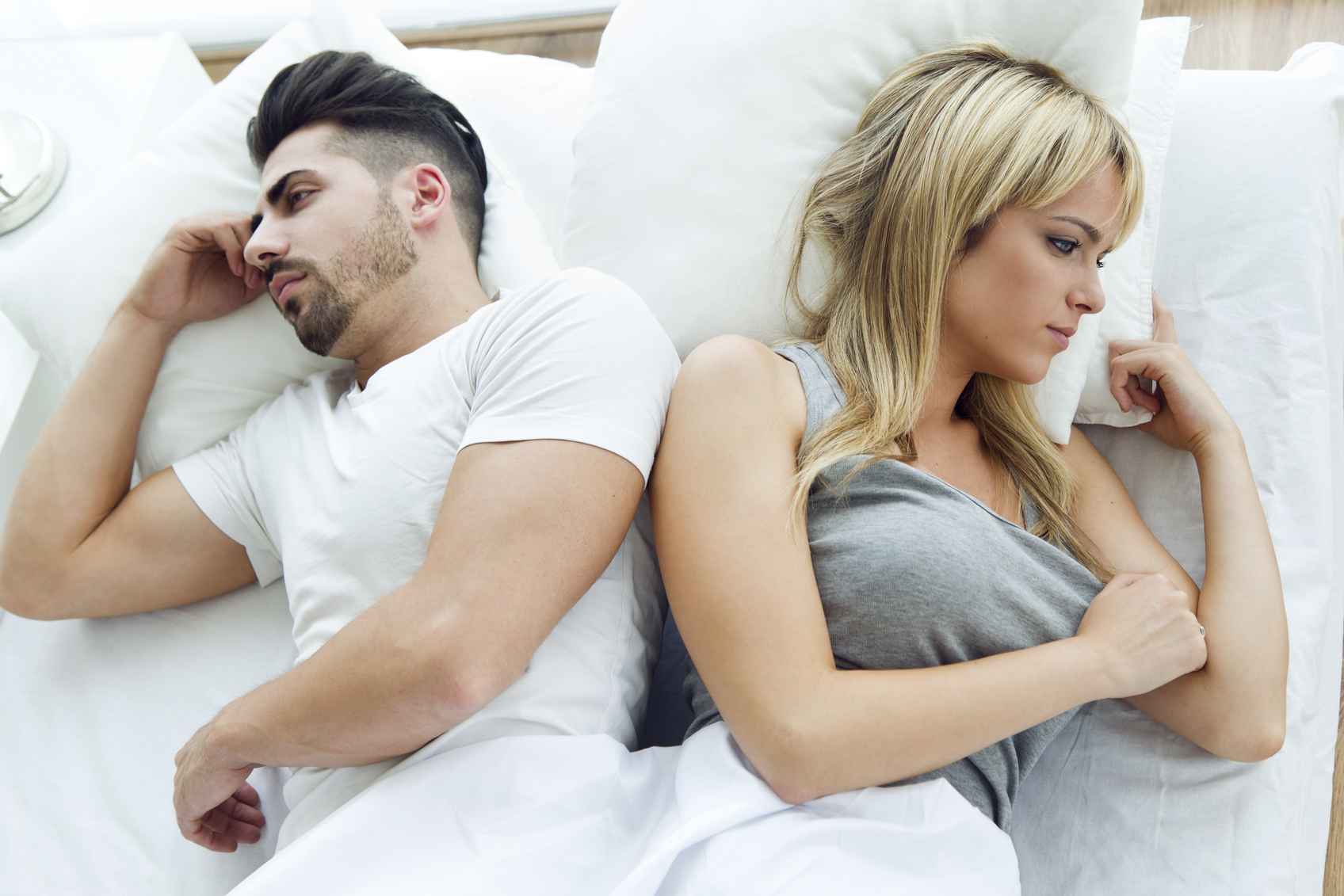 Portrait of upset couple lying back to bed