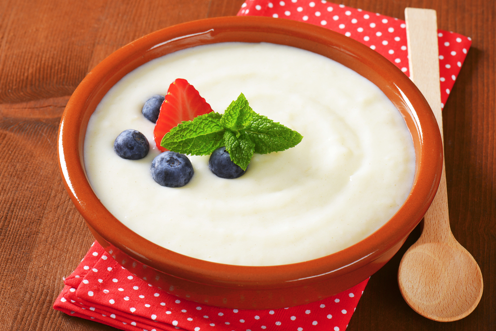 Smooth semolina porridge served in terracotta dish with fresh fruit